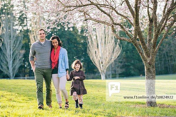 Junges Paar und Tochter beim Spaziergang im Frühlingspark