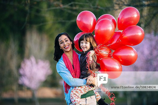 Portrait of young woman and daughter with bunch of red balloons in park