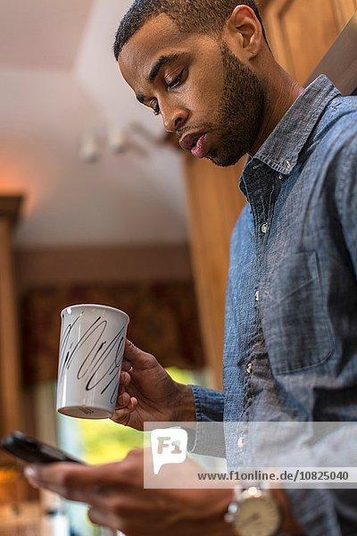 Mittlerer Erwachsener Mann in der Küche liest Smartphone-Text