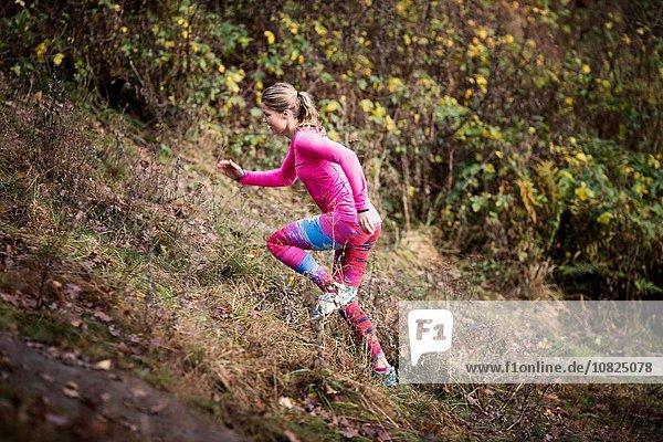 Seitenansicht der jungen Frau in Sportbekleidung beim Bergauflaufen