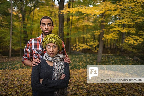 Porträt eines mittleren erwachsenen Paares  das im Herbstwald steht.