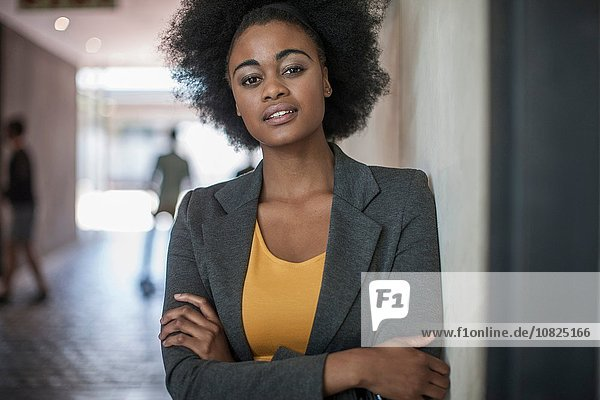 Portrait of confident young businesswomen leaning against office wall
