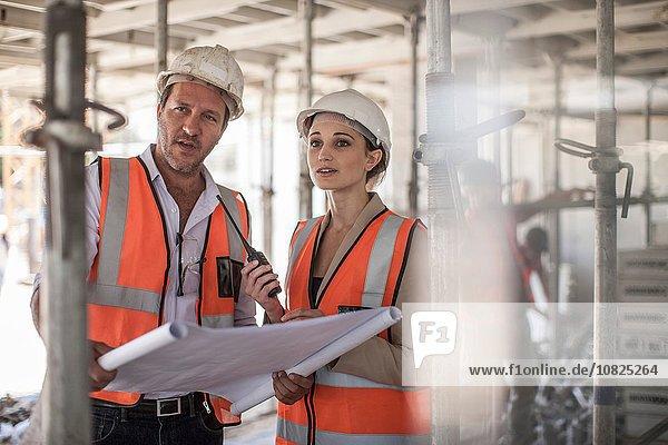 Weibliche und männliche Bauherren mit Bauplan auf der Baustelle