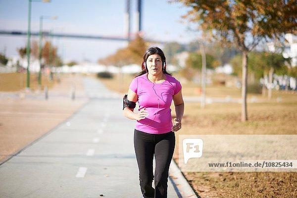Vorderansicht der reifen Frau mit Kopfhörer und Armband Jogging auf dem Pfad