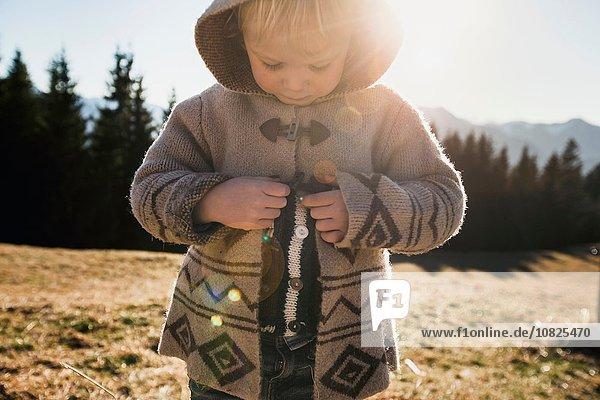 Female toddler fastening hooded jacket  Tegernsee  Bavaria  Germany