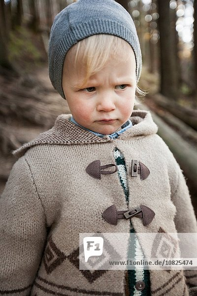 Portrait of frowning female toddler wearing knit hat in forest