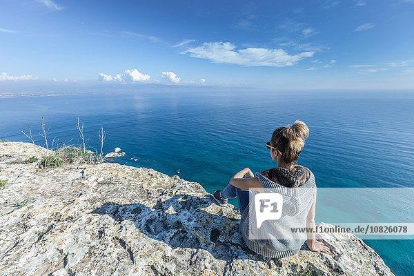 Rückansicht einer jungen Frau auf einer Klippe mit Blick auf das Meer  Cagliari  Sardinien  Italien