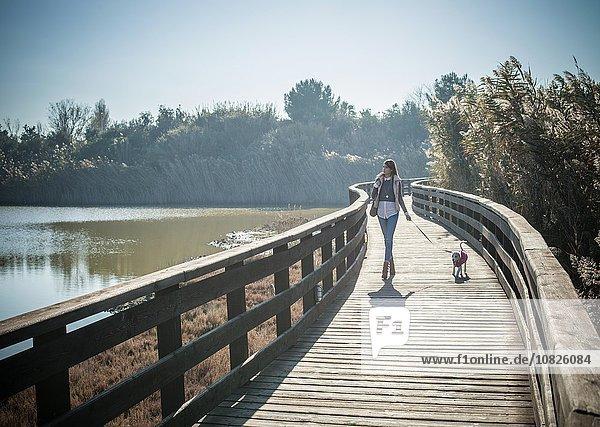 Durchgehende Vorderansicht der jungen Frau mit erhöhtem Holzsteg und Spaziergang