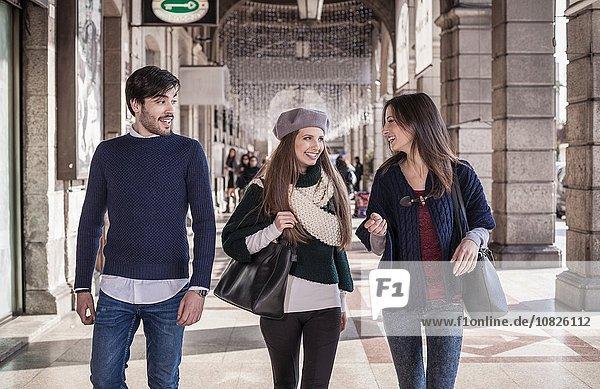 Frontansicht von Freunden  die Seite an Seite im Einkaufszentrum lächelnd spazieren gehen