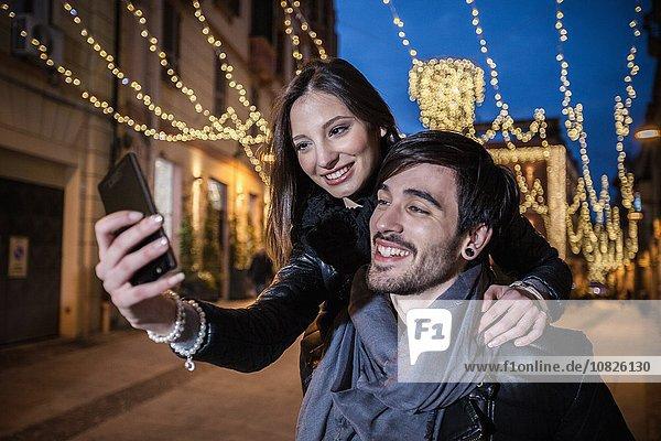 Junger Mann gibt junge Frau Huckepack mit Smartphone zu nehmen Selfie  lächelnd
