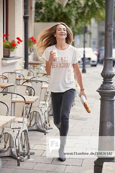 Durchgehende Vorderansicht einer jungen Frau  die mit Baguette und Einwegbecher auf dem Bürgersteig geht.