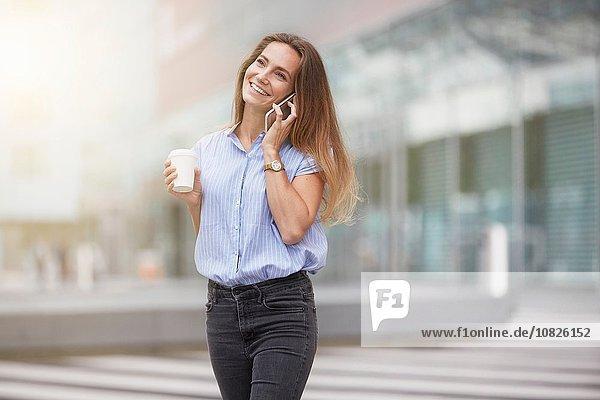 Junge Frau telefoniert mit dem Smartphone und schaut lächelnd weg.