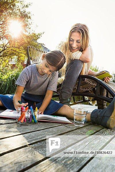 Tochter sitzend auf Holzdielenzeichnung mit Mutter