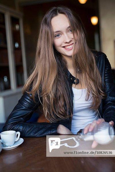 Porträt einer fröhlichen erwachsenen Frau  die Zuckerherz auf den Kaffeetisch gießt.