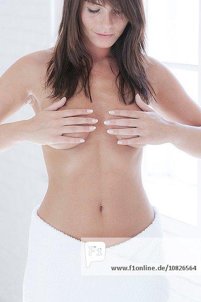 Junge nackte Frau mit Händen  die die Brüste berühren