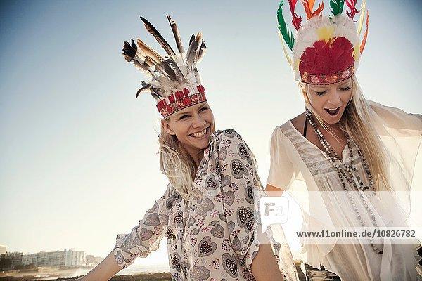 Junge Frauen in Federkopfbedeckungen tanzen im Sonnenlicht und sehen die Kamera lächelnd an.