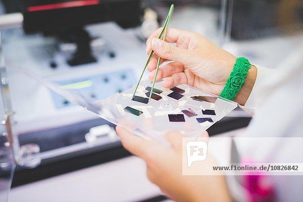 Female scientist using FTIR spectrophotometer  taking thin film sample for measurement