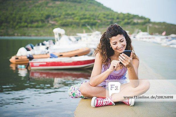 Frau an der Küste  Blick auf Smartphone