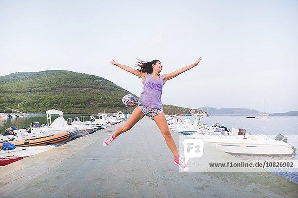 Frau an der Küste  springend in der Luft