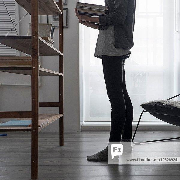 Ausschnitt einer Frau  die Bücher im Bücherregal des Wohnzimmers arrangiert.