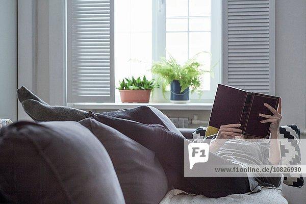 Frau liegt auf dem Wohnzimmersofa und liest ein Buch.