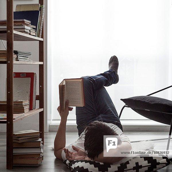 Mann  der auf dem Wohnzimmerboden liegt und ein Buch liest.