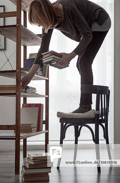 Frau auf Stuhl stehend  um Bücher im Bücherregal des Wohnzimmers zu arrangieren.