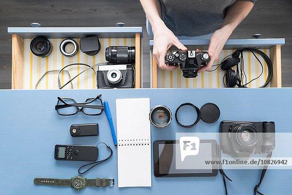 Draufsicht auf die Hände von Fotografinnen  die die Kamera aus der Schreibtischschublade im Studio nehmen.