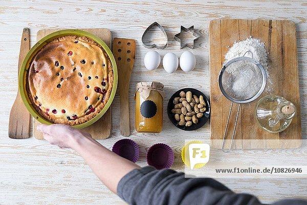 Draufsicht auf die weibliche Hand  die den gebackenen Kuchen an der Küchentheke aufhebt.
