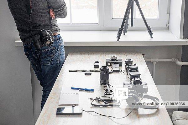 Fotograf neben der Fotoausrüstung auf dem Studiotisch