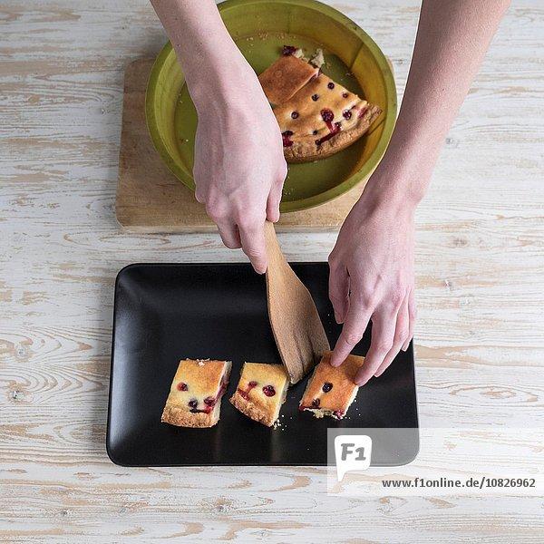 Draufsicht auf die weiblichen Hände  die den Kuchen auf die Schüssel an der Küchenzeile legen.