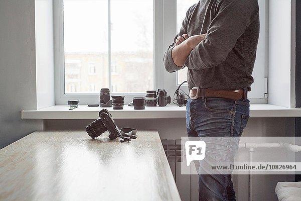 Männlicher Fotograf steht neben der Kamera auf dem Studiotisch