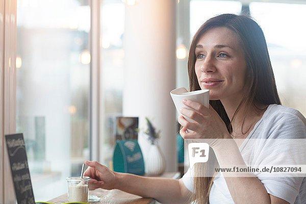 Junge Frau blickt durch das Caféfenster hinaus