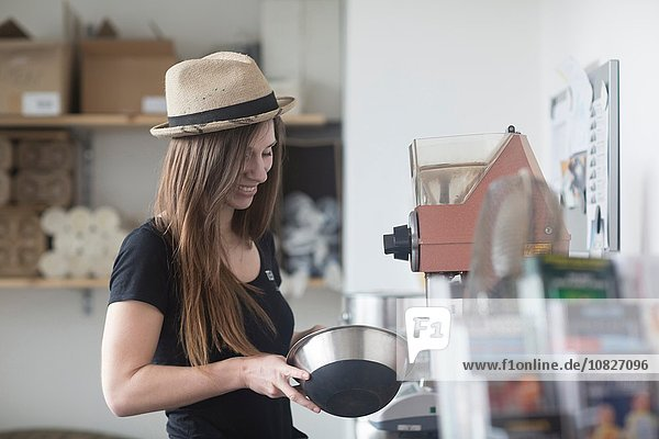 Young female waitress preparing food behind counter in cafe