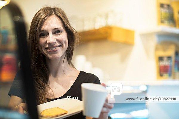 Porträt einer jungen Kellnerin mit Kaffee und Kuchen im Café