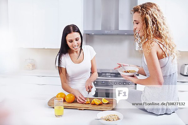 Zwei junge Freundinnen bei der Zubereitung von Frühstücksorangen an der Küchentheke