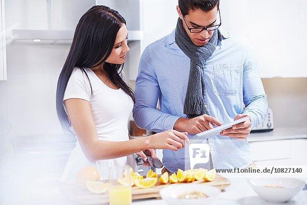 Junges Paar mit digitalem Tablett an der Küchenzeile