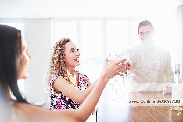 Three young adult friends making a white wine toast at kitchen counter