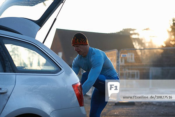 Runner with leg raised on car boot tying shoelace