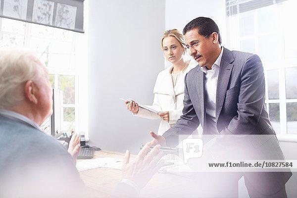 Geschäftsmann und Geschäftsfrau im Büro im Gespräch mit dem Senior-Kunden