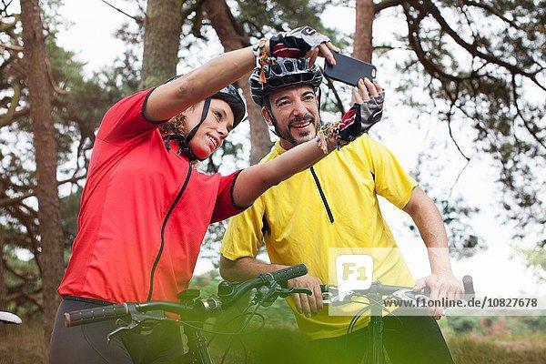 Glückliches Mountainbike-Pärchen mit Smartphone-Selfie im Wald
