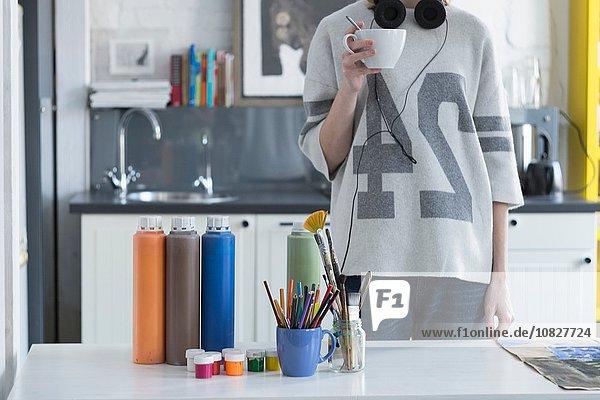 Künstlerin beim Kaffeetrinken am Küchentisch