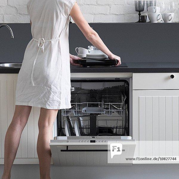 Rückansicht der Frau  die Geschirr in den Geschirrspüler lädt