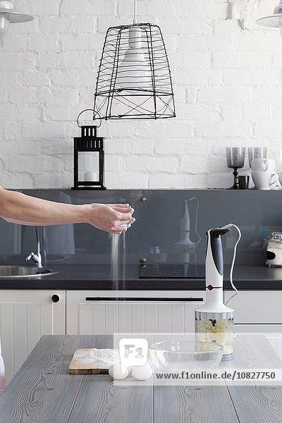 Womans Hände streuen Mehl über Schneidebrett am Küchentisch