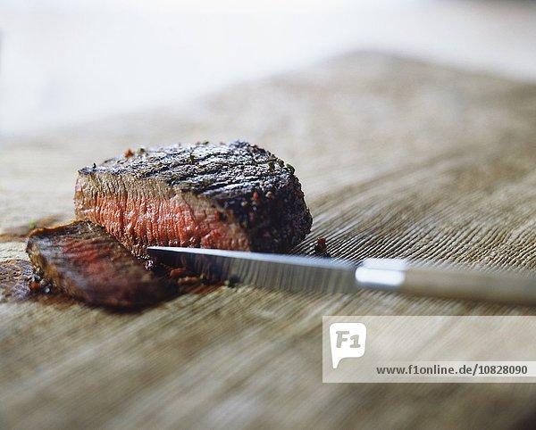 Mittelgroßes Steak mit Pfefferkörnern  geschnitten mit Messer