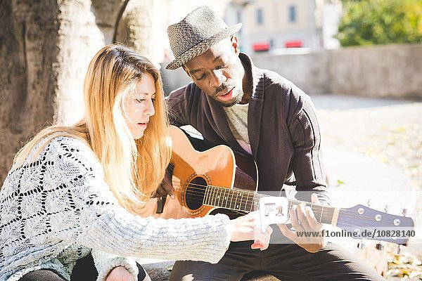 Couple learning to play guitar in park