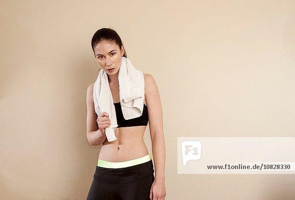 Junge Frau in Sportkleidung  Handtuch auf den Schultern mit Blick auf die Kamera