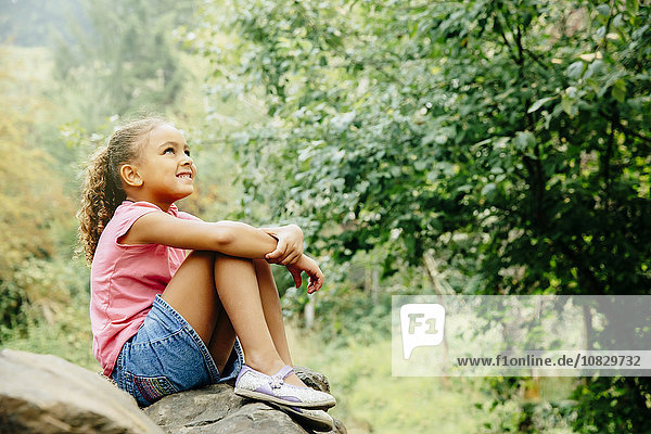 Mixed race girl sitting outdoors