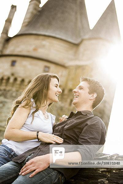 Caucasian couple smiling at castle