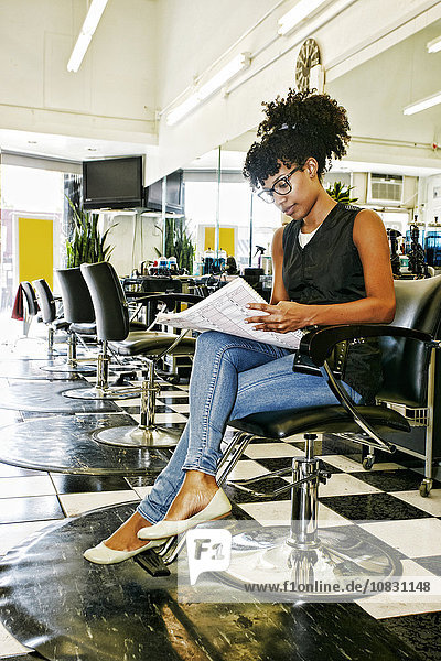 Mixed race hairstylist reading in salon